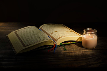 The Qur'an, the holy book of Islam. Kekhusyuan worship month of Ramadan, reading the scriptures by using a candle light.