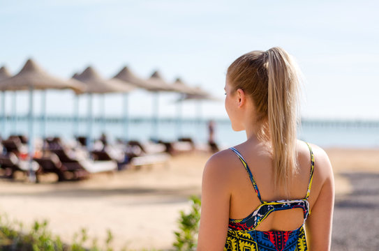 Young woman with ponytail, blonde hair is looking on the sea horizon, vacation mood, summer travel concept. Beach umbrellas on the background