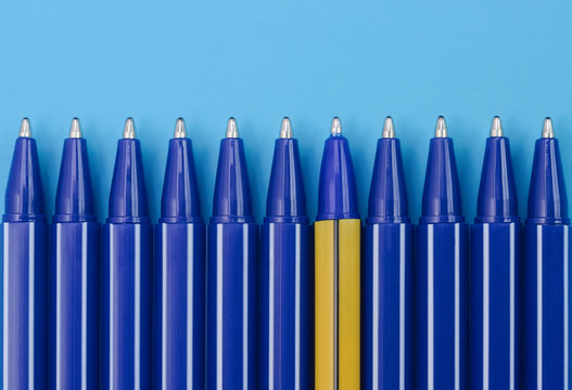 Blue pens and one yellow pen on blue background. Top view. Individuality concept.