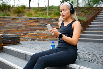 Beautiful sports woman sitting at stairs listen to music from smartphone
