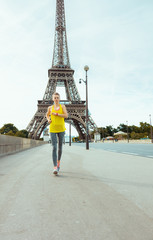 woman against clear view of Eiffel Tower jogging