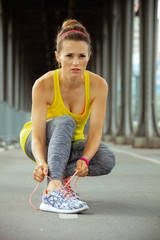 active woman looking into distance and tying shoelaces