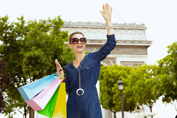 woman with shopping bags and smartphone waving with hand