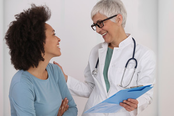 Mature Doctor comforting young Woman Patient. Good news concept. Professional medical help,support, advice Female health , gynecology concept