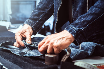Fashion designer is measuring jeans by meter