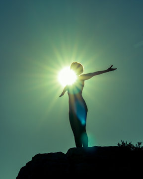 Silhouette of Yoga Fitness Woman Standing on Rock Performing Angel Pose (Asana) . She is Back Lit. Sun Flare Hitting Her Chest and Face in Center of Image. Copy Space.