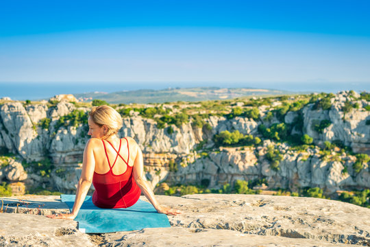 Yoga Fitness Woman Resting and Enjoying View after Training Session. Sitting at the Edge of Cliff Overlooking Mountain Range and Ocean in Far Distance.