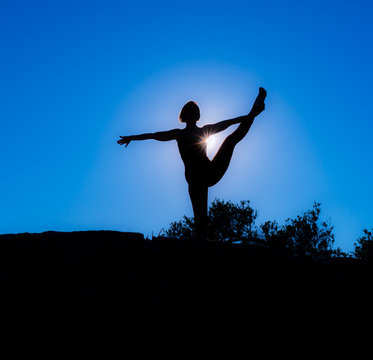 Silhouette of Yoga Fitness Woman Standing on Rock, Doing Extended Tree Asana (Pose). She is Back Lit. Sun Flare Hitting Her Chest. Copy Space.