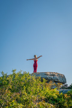 Yoga Fitness Woman Standing on Large Rock Stretching Arms Wide. Copy Space.