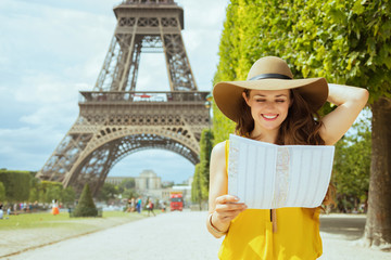 happy young solo tourist woman looking at map