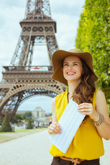 traveller woman against Eiffel tower with map having excursion
