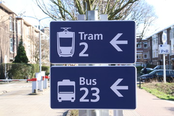 Blue and white sign with direction to the tram and bus at station Laan van NOI in Den Haag