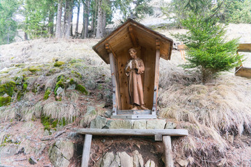A wood carved catholic statue of a holy monk in the forest of tyrol in the dolomites