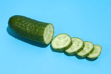 Ripe green cucumber on blue background. Healthy eating and dieting concept.