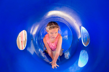 6 year old girl playing in blue plastic tube