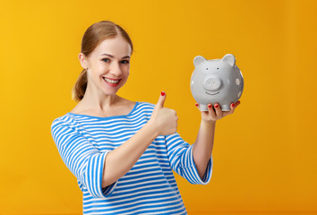 happy woman with piggy money bank on pink background. financial planning concept
