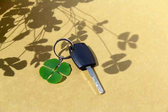 Key car and clover leaf. 4-leaf clover and car key on paperboard background with clover shadow.