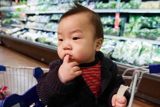 쇼핑카트에 앉아 손가락을 빨며 고민중인 아기