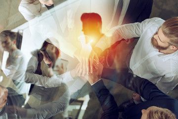 Business people putting their hands together. Concept of startup, integration, teamwork and partnership. Double exposure.