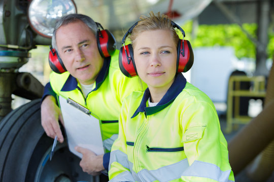 two workers with earmuffs observing something