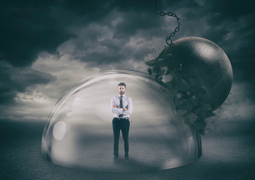 Businessman safely inside a shield dome during a storm that protects him from a wrecking ball. Protection and safety concept