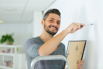 happy repairman putting picture frame onto wall