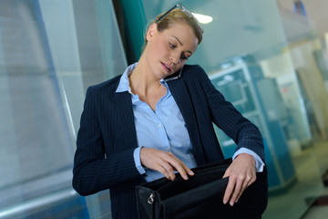 businesswoman looking in bag while taking telephone call