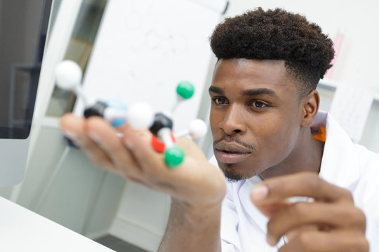 male doctor or scientist touching dna molecule model