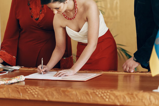 Happy beautiful bride in elegant white dress signing marriage contract during wedding ceremony in registry office, newlywed family moment