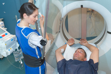 nurse guiding patient entering mri scanner