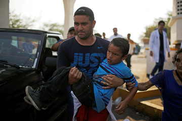 Central American migrant carries a child who was injured while trying to flee during an immigration raid in an old government facilty during their journey towards the United States, in Huixtla