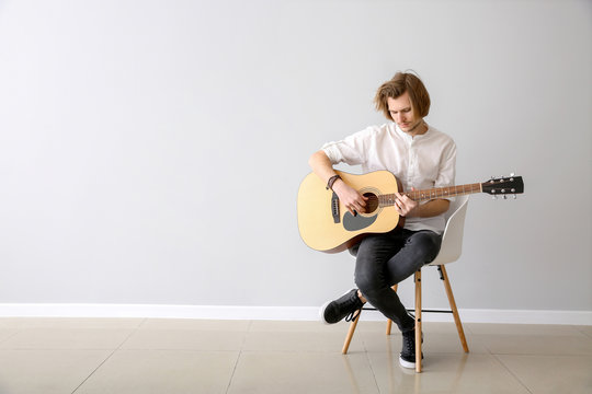 Handsome young man playing guitar near light wall