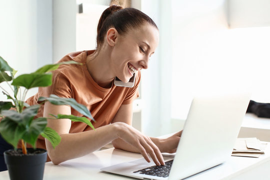 Woman talking by phone while working on laptop indoors