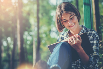 Pretty girl with notebook and pen make a shortnote while travel education along path of a big forest.