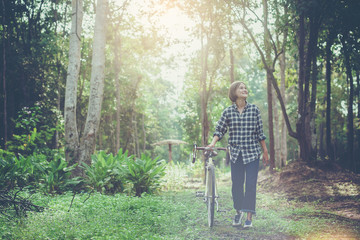Happiness girl with bicycle walking relax and enjoy along a path in big forest