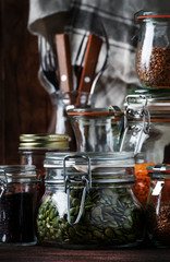 Food set. Raw cereals, pasta, groats, organic legumes and useful seeds in glass jars. Vegan source of protein and energy resources. Rustic wooden kitchen table background.