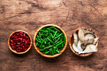 Food cooking background, ingredients for preparation vegan dishes, green bean, mushrooms. Healthy vegetarian food concept. Rustic wooden table, top view, copy space