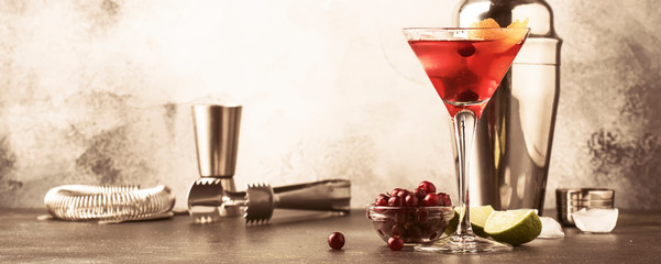 Cosmopolitan cocktail with vodka, liqueur, cranberry juice, lime, ice and orange zest, gray bar counter background, bartender tools, copy space, toned banner
