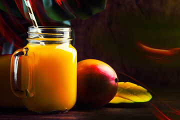 Mango smoothie jar with fresh fruit on rustic wooden background, copy space, summer drink concept