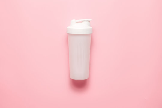 White plastic sports shaker on pastel pink  background.  Trendy athletics and sport minimal  concept. Female fitness.Flat lay, top view.