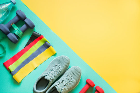 Sport and fitness equipment, dumbbells, fitness shoes, measuring tape on punchy yellow.