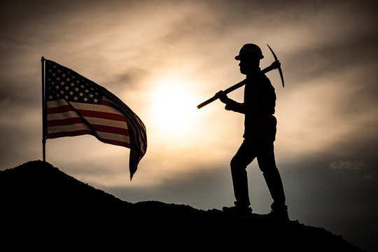 Concept Labor Day: Labor man standing holding a pickaxe with the United States flag