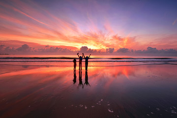 Wall Mural - Silhouette of kids standing over the beach with beautiful sunset reflections