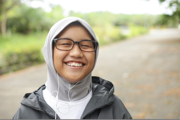 Happy Asian Muslim Girl Listening to Music in the Park