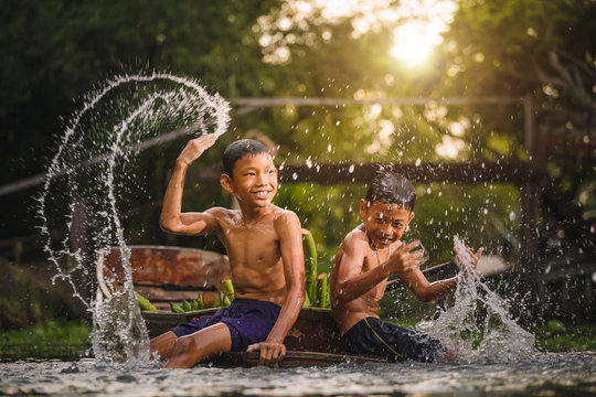 Two boys splashing in water near the Damnoen Saduak Floating Market