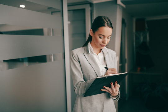 Caucasian successful businesswoman in formal wear standing at lobby in firm and writing on clipboard. Some people dream of success while others wake up and work.
