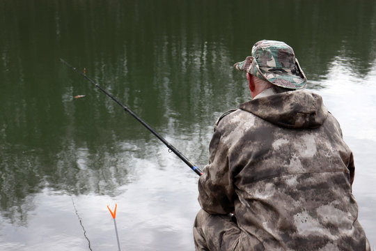 Fisherman in hunting clothes sitting with a fishing rod on the shore. Man angling on the lake in spring, trees are reflected in the water