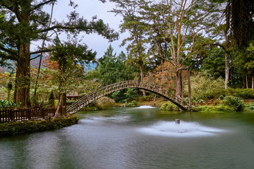 Beautiful wooden arch bridge scenics at University pond in Xitou Nature Education Area at Nantou Lugu, Taiwan.