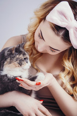 Wall Mural - portrait of a beautiful cute girl with a cat in hands,young woman in a headband for make up on a gray studio background with a kitten, concept natural beauty, cosmetics, body care