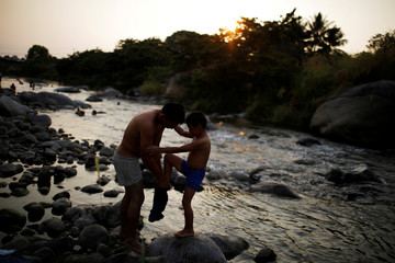 A migrant from Honduras helps his child get dressed after a bath in a river during a break in his journey towards the United States, in Huixtla